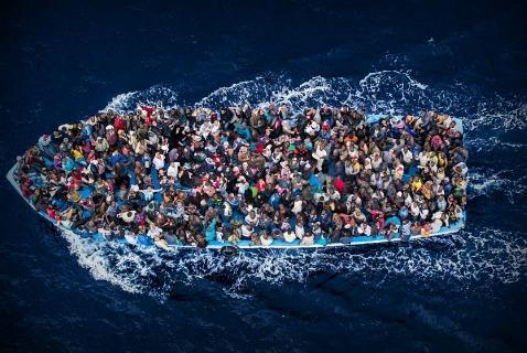 Итальянский флот следит за лицами на лодке у берегов Африки в Средиземном море