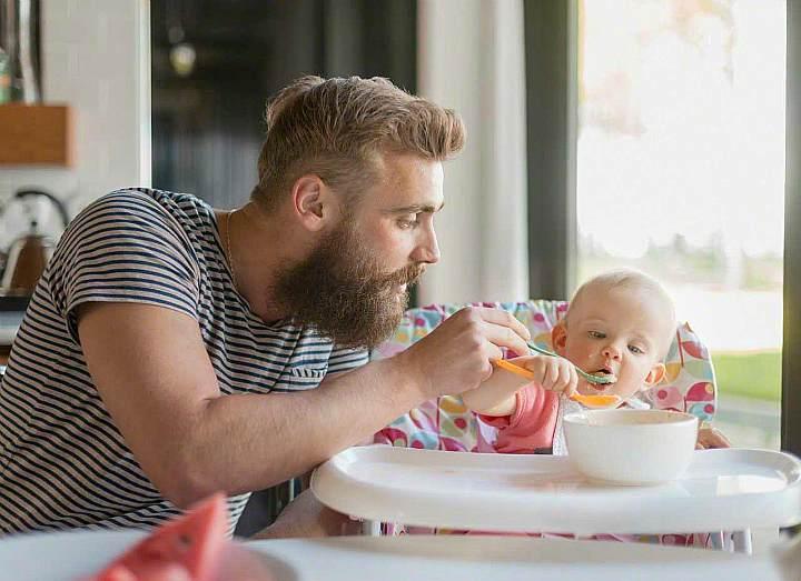 Отец кормит сына