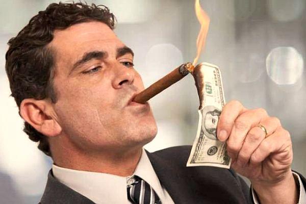 Бизнесмен прикуривает от стодолларовой купюры